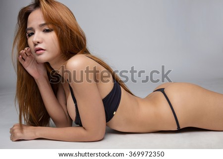 Portrait of beautiful sexy young woman wearing black thong lying on the floor. - stock photo