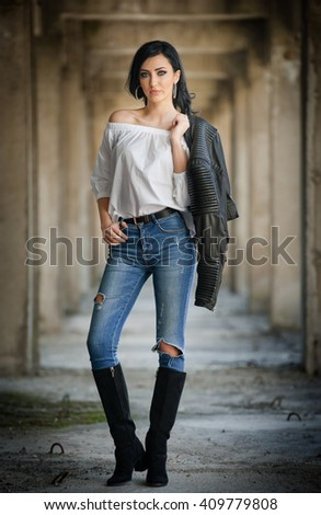 Portrait of beautiful sexy young woman with modern outfit, leather jacket, jeans, white blouse and black boots, in urban background. Attractive young brunette with long hair and blue eyes posing.