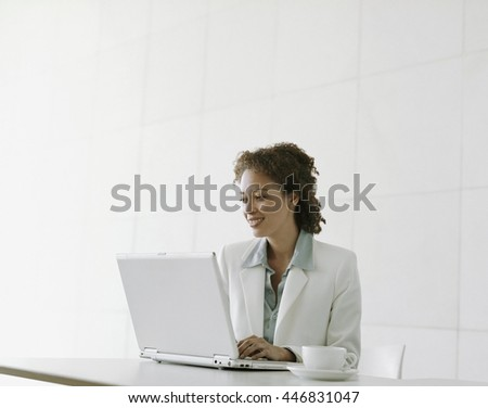 Portrait of beautiful smiling afro-american office worker sitting at desk, using computer.
