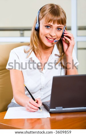 Portrait of beautiful smiling blond businesswoman in gray suit holding a pen in her hand and touching headset working on the lap top