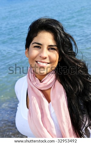 Portrait of beautiful smiling brunette girl at beach