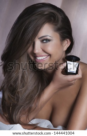 Portrait of beautiful smiling brunette woman holding bottle of perfume. Looking at camera. - stock photo