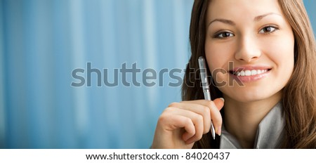 Portrait of beautiful smiling businesswoman with pen at office.To provide maximum quality, I have made this image by combination of two photos. You can use left part for slogan, big text or banner. - stock photo