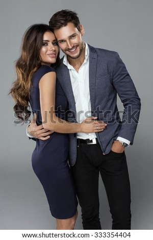 Portrait of beautiful smiling couple. Handsome man in jacket hugging his girlfriend - stock photo