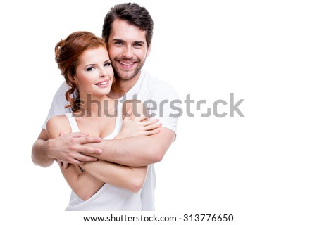 Portrait of beautiful smiling couple posing at studio over white background.