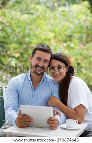 Portrait of beautiful smiling couple with tablet computer sitting in outdoor cafe