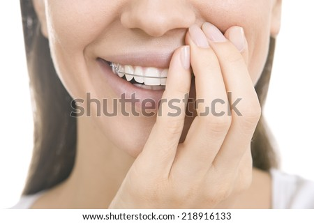 Portrait of Beautiful smiling girl covering with hand her retainer for teeth, isolated on white background