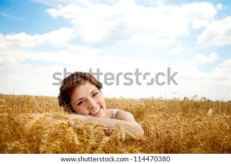 Portrait of beautiful smiling girl in wheat field