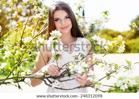 Portrait of beautiful smiling girl near blossom cherry tree brunch  in spring garden - stock photo