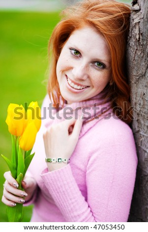 Portrait of beautiful smiling girl with spring flowers posing in park - stock photo