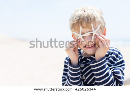 portrait of beautiful smiling happy boy covering his eyes with starfish at the beach, vacation and lifestyle concept, copyspace on the side - stock photo
