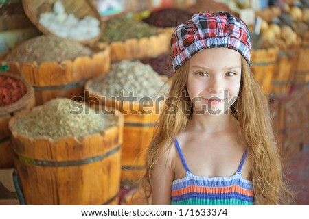Portrait of beautiful smiling little girl against background of wooden barrels and spices.