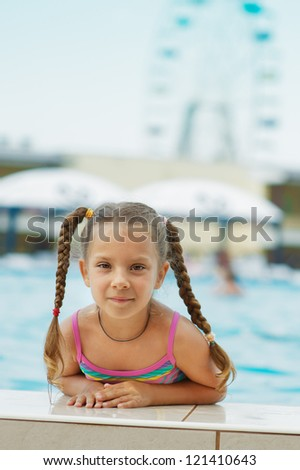 Portrait of beautiful smiling little girl at resort in warm comfortable pool.