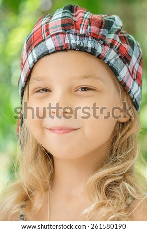 Portrait of beautiful smiling little girl in green summer city park. - stock photo