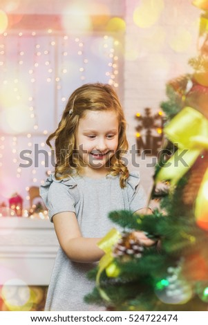 Portrait of beautiful smiling little girl over fireplace and window with garland background. Happy child decorating big Christmas pine tree for holiday celebration at home interior