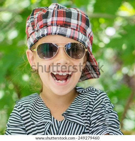 Portrait of beautiful smiling little girl with sunglasses in green summer city park. - stock photo