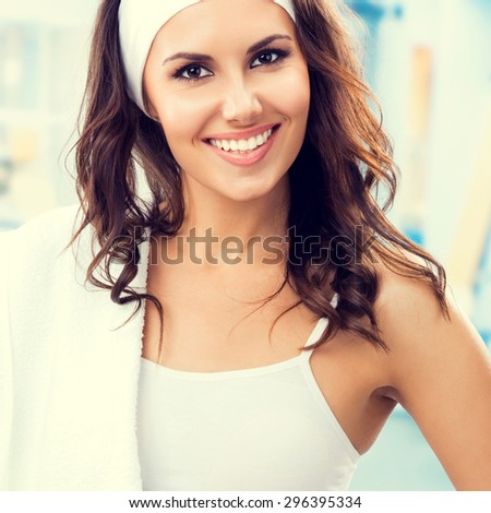 Portrait of beautiful smiling lovely woman at fitness club or gym - stock photo