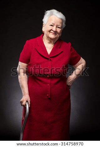 Portrait of beautiful smiling old woman on a dark background - stock photo