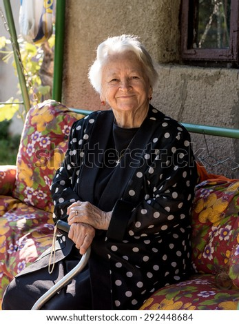 Portrait of beautiful smiling old woman outdoors - stock photo
