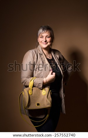 portrait of beautiful smiling plus size young blond woman posing with designer handbags - stock photo
