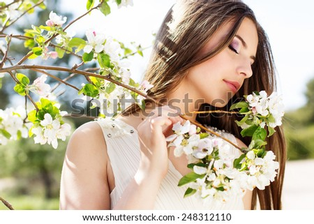 Portrait of beautiful smiling pretty teenager girl near blossom cherry tree brunch  in spring garden - stock photo