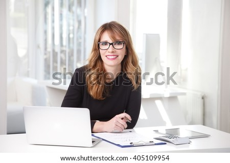 Portrait of beautiful smiling professional woman sitting at her workplace in front of laptop and working on new project.