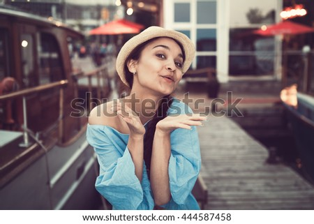 Portrait of beautiful smiling white Caucasian brunette girl sending air kiss on boat yacht pier quay, in blue dress and straw hat, navy maritime retro vintage style concept - stock photo