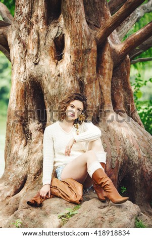 Portrait of beautiful smiling white Caucasian girl woman with long dark red brown hair, in shorts and sweater, sitting in summer park forest outside, toned with Instagram filters - stock photo
