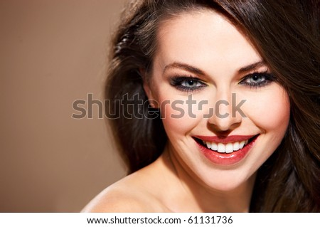 Portrait of beautiful smiling woman isolated on beige with copyspace - stock photo