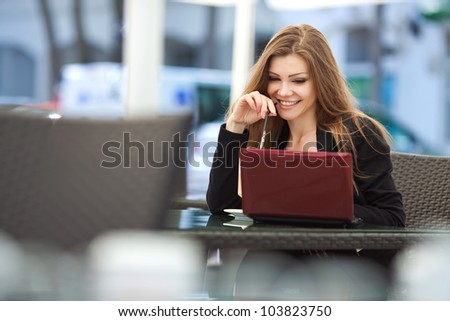 Portrait of beautiful smiling woman sitting in a cafe with laptop outdoor - stock photo