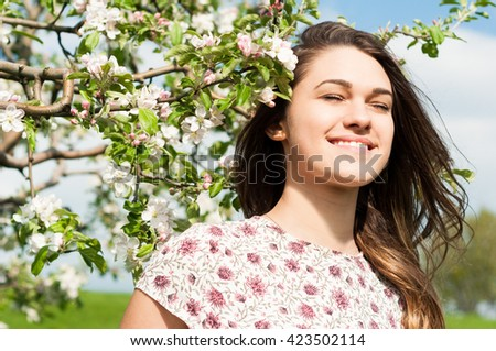 Portrait of beautiful smiling woman sitting in blooming garden as outdoor relaxation concept - stock photo