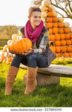 Portrait of beautiful smiling woman sitting on the bench and holding pumpkin in front of pumpkin rows on farm during the autumn season