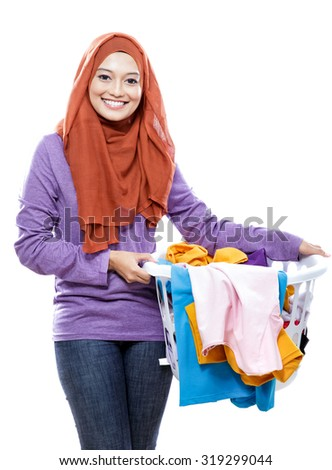portrait of beautiful smiling woman wearing hijab holding a laundry basket isolated on white background - stock photo