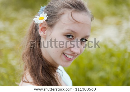 Portrait of beautiful smiling woman with flower in hairs - stock photo
