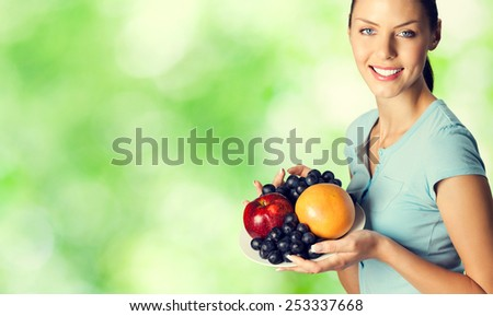 Portrait of beautiful smiling woman with plate of fruits, outdoors, with blank copyspace area for text or slogan - stock photo