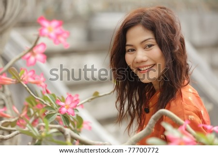 portrait of beautiful smiling woman with tropical flowers - stock photo