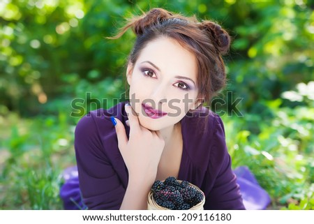Portrait of beautiful smiling young brunette woman posing with basket of blackberry  - stock photo