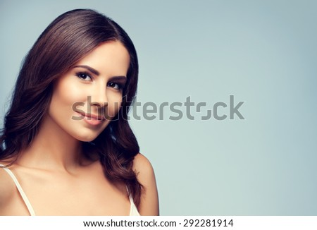 Portrait of beautiful smiling young brunette woman, with blank copyspace area for text or slogan - stock photo