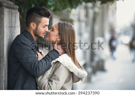 Portrait of beautiful smiling young couple outside, side view face to face. Happy couple in love outdoor on street. - stock photo