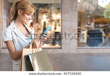 Portrait of beautiful smiling young tourist woman using a smart phone to network, shopping in a shopping mall with fashion store window in background, technology and consumer lifestyle, outdoors.
