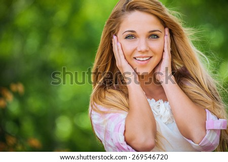 Portrait of beautiful smiling young woman, against green of summer park. - stock photo