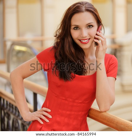 Portrait of beautiful smiling young woman in red dress which talks by mobile phone in big hall. - stock photo