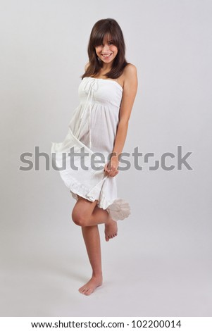 Portrait of beautiful smiling young woman standing in dress - stock photo