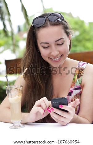 Portrait of beautiful smiling young woman, which talks by mobile phone - stock photo