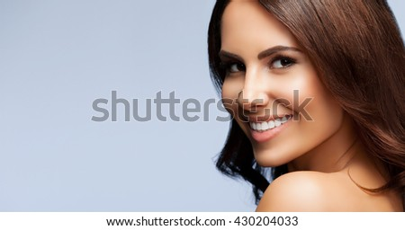 portrait of beautiful smiling young woman with naked shoulders, with copyspace, on grey background