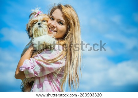 Portrait of beautiful smiling young woman with small dog, against blue sky. - stock photo