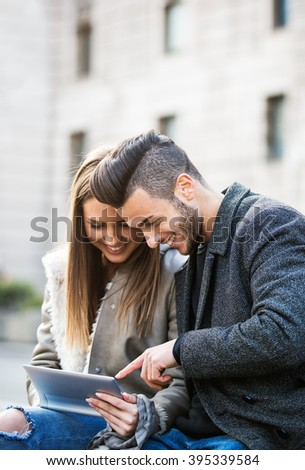 Portrait of beautiful smilling young couple using a digital tablet and enjoying together, sitting on a bench. Modern relationship concept. Websurfing. Toned photo added noise. - stock photo