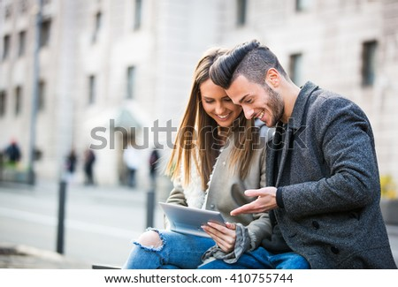 Portrait of beautiful smilling young couple using a digital tablet and enjoying together, sitting on a bench. Modern relationship concept. Websurfing - stock photo
