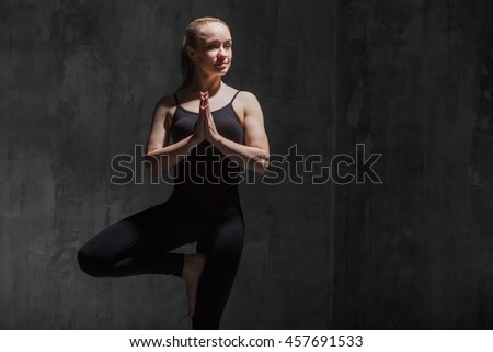 Portrait of beautiful sporty young woman in black sportswear working out indoors against grunge dark grey wall. Model doing Vrksasana Posture, Tree Pose. Copy space