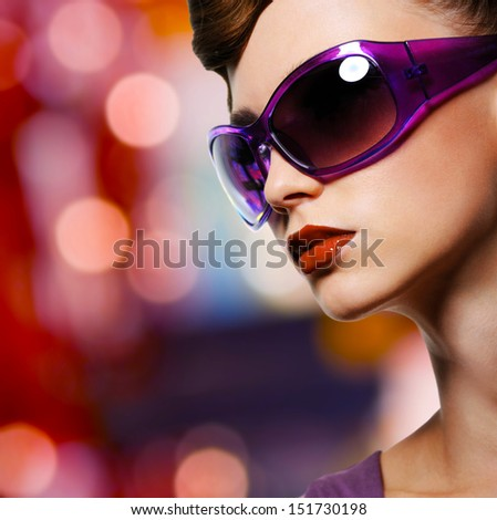 Portrait of beautiful stylish woman in fashion violet sunglasses - stock photo